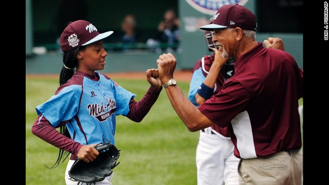 Pennsylvania pitcher Mo'ne Davis, left, celebrates with coach Leland Lott as she returns to the dugout at the end of the fifth inning during a baseball game against Tennessee in United States pool play at the Little League World Series tournament in South Williamsport, Pa., Friday, Aug. 15, 2014. Pennsylvania won 4-0, with Davis pitching a complete game two-hit shutout.(AP Photo/Gene J. Puskar)
